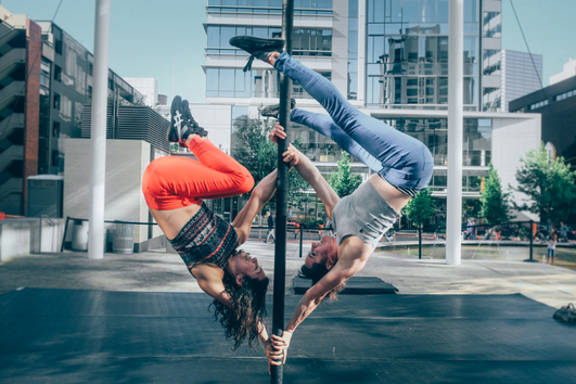 two dancers on a chinese pole performing outside