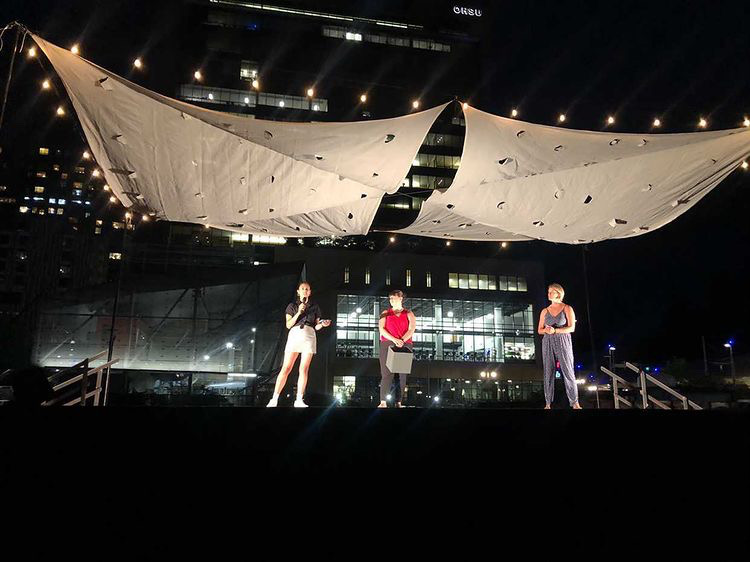 three people standing on a stage at night