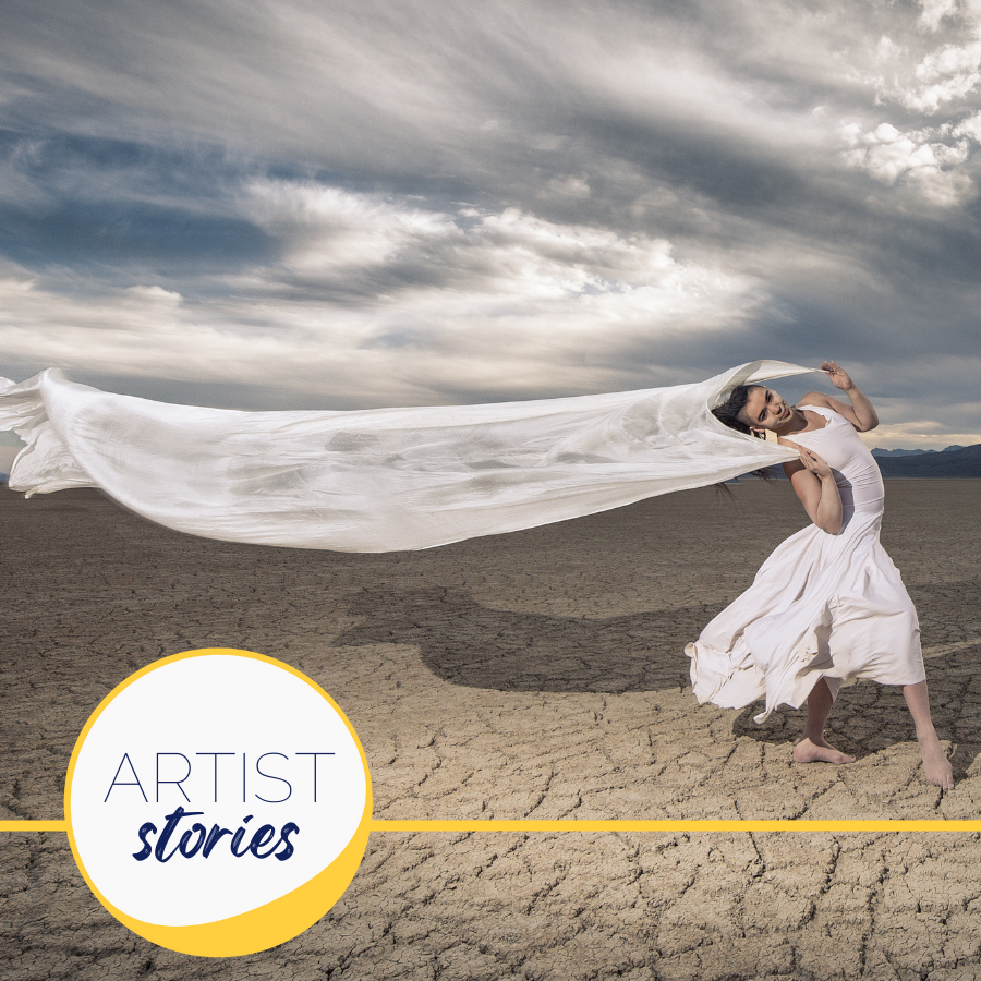 dancer in white on cracked earth with long billowy scarf