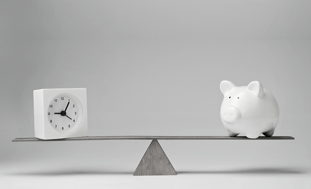 a clock and a piggy bank on opposite sides of a teeter totter